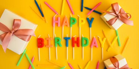 Happy Birthday candles on yellow background. Bright color wallpaper Candles with text Happy Birthday on yellow background Foto de archivo