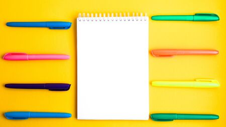 Note pad with empty space for text, colorful felt tip pens around on yellow background, copy space, office suplies