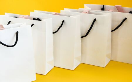 Set of white paper bags for shopping on yellow background. Mockup for design, copy space, shopping bag and copy space for plain text or product