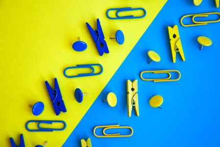 Office supplies in the form of colored buttons and paper clips, clothepins on yellow and blue background, copy space, border and frame, back to school concept of office chancery