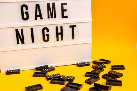 Game night text on lightbox with black dominoes on yellow background, table game, dominoes flying