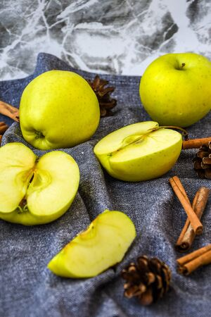 green golden apples or Granny smith with cinnamon sticks pine fir cones on kitchen towel, preparing food, dessert, healthy nutrition, autumn time