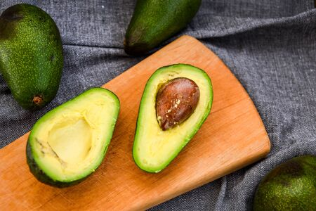 Avocado on a chopping wooden Board. avocado, vegetable, food, organic, green, vegetarian Halves fresh avocado