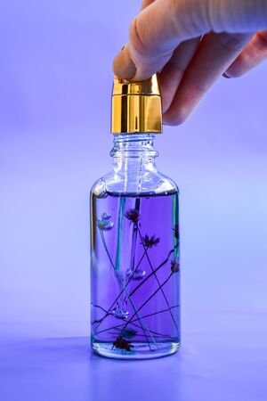 Anti aging serum in glass bottle with dropper on blue background. Facial liquid serum with collagen and peptides. Skin care essence for beautiful healthy skin. Dropper glass bottle mock-up.
