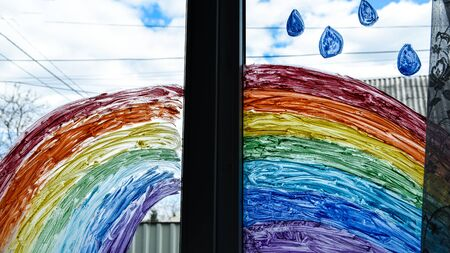 let's all be well. public flashmob children paint a rainbow on the windows waiting for the end of the quarantine pandemic coronavirus entertainment leisure home, copy space for text