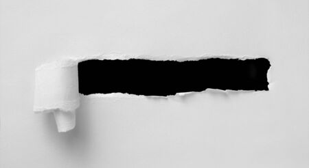 A hole in white paper with torn edges and a black isolated background inside, Ripped black and white paper, copy space