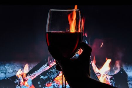 A glass of wine against the background of a burning fire. The atmosphere of rest and relaxation. Water drops, banner, christmas holiday, winter