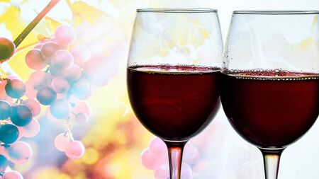 red wine in drinking glass next to grapes branches background, copy space, alcohol, A glass of fragrant red wine and bunches of blue grapes