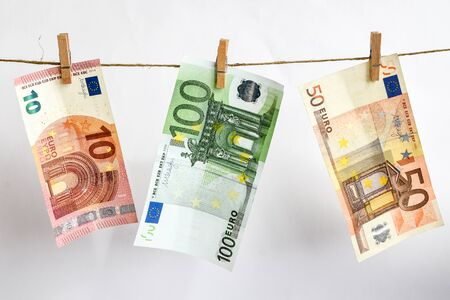 euros on a rope, euro with a clothespin on a rope isolated on a white background, Concept - money laundering. euro are dried on the ropes. euros after washing. Money earned honestly. Legalization of money. Bundles of notes attached to the rope with signs