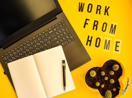 Text WORK FROM HOME with notebook, laptop and pen, cactus, work from home place, freelance environment on yellow background copy space, planning day, to do list