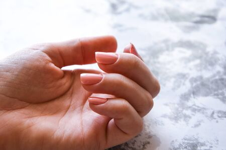 Beautiful natural nails manicure gel on pink color, manicured hands with white, copy space for text