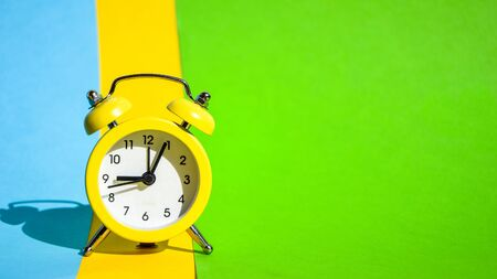 Yellow vintage alarm clock on a blue and yellow and green background with selective focus, copy space for text, The concept of time, delay, morning rise, the appointed meeting, Ringing twin bell vintage classic alarm clock, Rest hours time of life good morning night wake up awake concept.