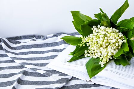 Bouquet of a white lilies of the valley on the open book on the towel in strip, soft focus. Spring flowers education, and reading, stay home