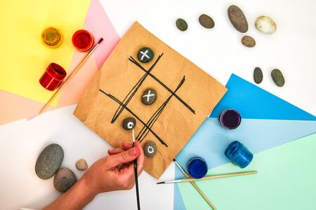 top view of tic tac toe game with stones marked with naughts and crosses. Children's art project, a craft for children. DIY concept. Step by step photo instructions Step 6