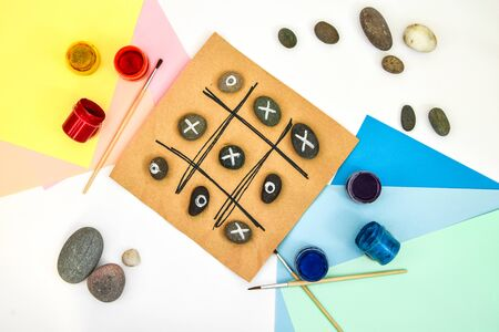 top view of tic tac toe game with stones marked with naughts and crosses. Children's art project, a craft for children. DIY concept. Step by step photo instructions