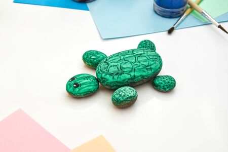 Painting a rock green turtle on a stone step by step. Children art project. DIY concept. Step by step photo instruction.View from above. Work with children and adults in quarantine.