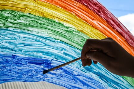 hand painting rainbow on a window, stay home during quarantine, Image of kids leisure at home, Chase the rainbow flashmob Фото со стока