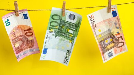 euros on a rope, euro with a clothespin on a rope isolated on a yellow background, Concept - money laundering. euro are dried on the ropes. euros after washing. Money earned honestly. Legalization of money. Bundles of notes attached to the rope with signs