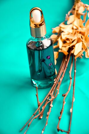 Anti aging serum in glass bottle with dropper on purple background and dry flowers . Facial liquid serum with collagen and peptides. Skin care essence for beautiful healthy skin. Dropper glass bottle mock-up.