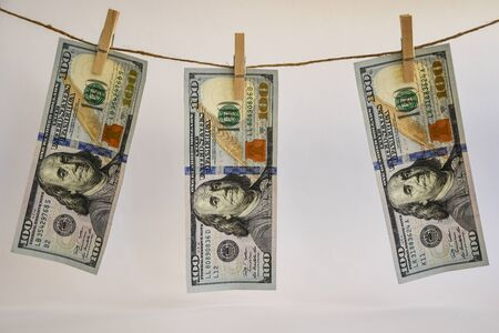 100 dollars on a rope, dollars with a clothespin on a rope isolated on a white background, Concept - money laundering. Dollars are dried on the ropes. Dollars after washing. Money earned honestly. Legalization of money. Bundles of notes attached to the rope with signs Stock Photo