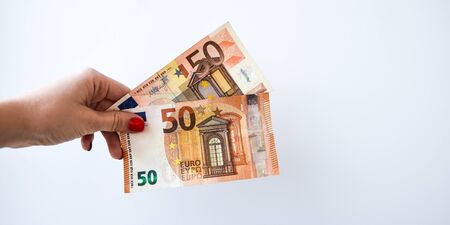 Woman's hand with 50 euros money on a white background, copy space for text, Close up of female hands counting 50 euro banknotes isolated on white background