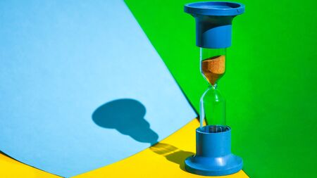Hourglass colored background, copy space for text, Hourglass shows that time is running out, sand glass, The concept of time, delay, morning rise, the appointed meeting