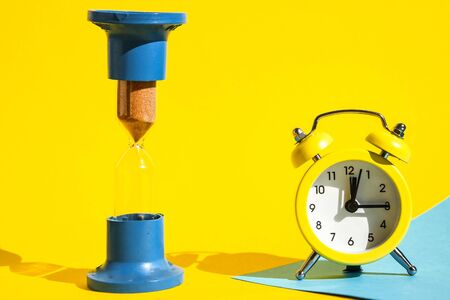 classic desktop clock, Hourglass colored background on yellow and blue, copy space, The concept of time, delay, morning rise, the appointed meeting, Ringing twin bell vintage classic alarm clock and sand clock
