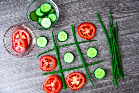 Diet concept hazardous game for health tic tac toe made of tomatoes cucumbers and green onion, vegan vegetarian food
