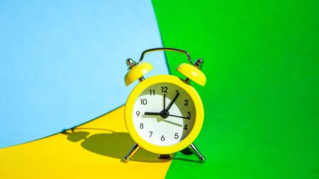 Yellow vintage alarm clock on a blue and yellow and green background with selective focus, copy space for text, The concept of time, delay, morning rise, the appointed meeting, Ringing twin bell vintage classic alarm clock, Rest hours time of life good morning night wake up awake concept. 写真素材