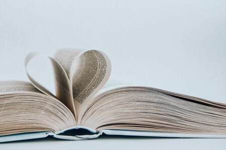 Book with love symbol isolated on white background, Love books, love to read, love stories, heart shape from paper book, Romantic background with the book