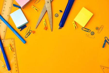 School supplies on yellow background, copy space, scissors, pen, paper clips, ruller, stickers. Back to school, Study at home