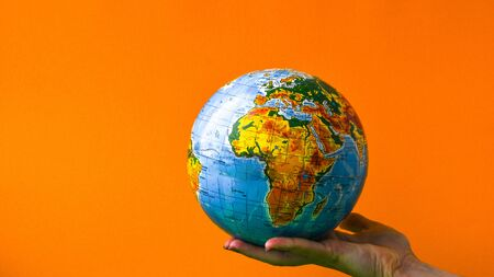 The globe in children's hands on colorful background. Copy space for text. World globe on a palm. Globalization Concept. Environmental conversation