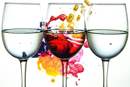Three wine glasses in a row with colorful light painting behind, Set of three wine glasses with red, white and rose wine, banner, alcohol drinks 版權商用圖片