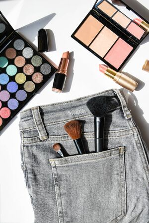 Different makeup products composition with jeans on white background, flat lay, top view, eyeshadow, lipstick, highlighter, make up brushes on jeans pocket