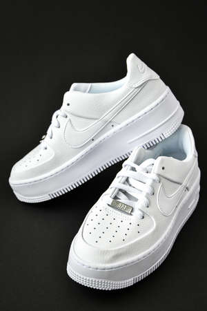 Zhytomyr, Ukraine - June 1, 2020: Nike Air Force 1 Sage white sneakers product shot on black background. Illustrative editorial photo. Sport footwear