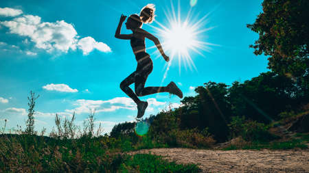 Silhouette of girl jumping in mountains against blue sky and hard sun light. doing outdoor sport stretch. practicing yoga.