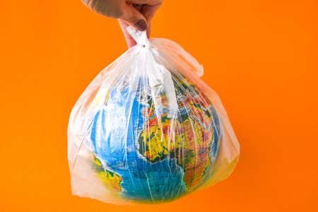 ball in the form of a globe is in a plastic bag. concept of plastic pollution of the earth. World Environment Day concept.Toy world globe in white plastic bag. Copy space for text. Save Earth