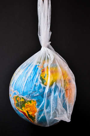 ball in the form of a globe is in a plastic bag. concept of plastic pollution of the earth. World Environment Day concept.Toy world globe in white plastic bag. Copy space for text. Save earth 写真素材