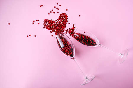 two champagne glasses with confetti in shape of heart isolated on an empty pink festive background, copy space, valentines day holiday festive card 免版税图像