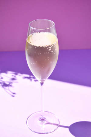 Champagne glass on color defocused background, copy space for text, party celebration, alcohol beverage