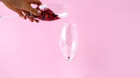 red confetti fall into champagne glass on pink background, copy space for text, creative holiday festive card, valentines day