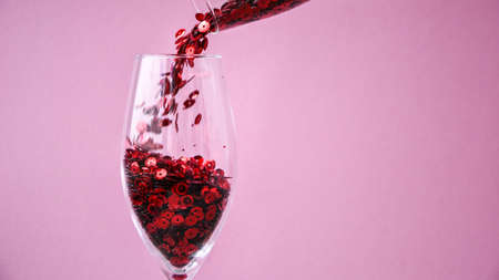 banner red confetti fall into champagne glass on pink background, copy space for text, creative holiday festive card, valentines day 免版税图像