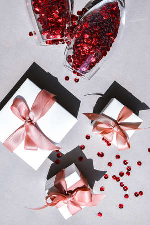two champagne glasses with confetti and gift boxes isolated on an empty pink festive background, copy space, valentines day, Christmas and New Year or holiday festive card 免版税图像