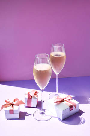 Champagne glass with gift boxes on color defocused background, copy space for text, party celebration, alcohol beverage 免版税图像