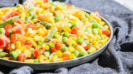 Mixed frozen vegetables in a plate. Stocking up vegetables for winter storage. Assortment of frozen vegetables