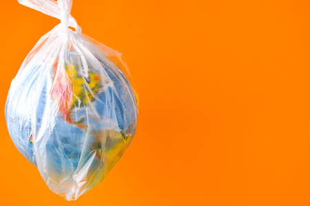 ball in the form of a globe is in a plastic bag. concept of plastic pollution of the earth. World Environment Day concept.Toy world globe in white plastic bag. Copy space for text. Save earth Stock fotó