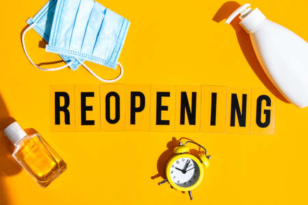 Words reopening text on the light box. New life, new business, new deals concept. Alarm clock. New normal. Yellow background