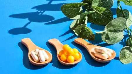 Pills on wooden spoon on blue background. Hard light and shadows. Creative minimalism concept. Vitamins and prebiotics, probiotics. Autumn vitamin dose. Eucalyptus