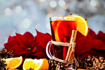 Christmas drink. Glasses of hot mulled wine with oranges, anise and cinnamon next to the red poinsettia flower. Holiday atmosphere, Rustic style. The idea for creating greeting cards