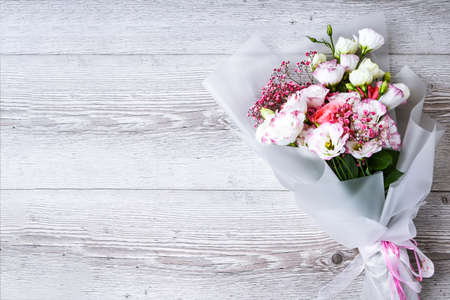 top view of bouquet of flowers on white wooden background. copy space for text, holiday concept, greeting card. cover